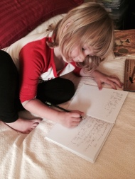 Emma writes in her notebook.